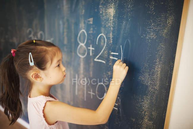 Chica escribiendo en tiza en una pizarra - foto de stock
