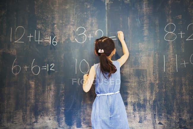Девушка пишет мелом на доске . — стоковое фото