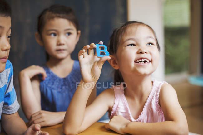 Niños sosteniendo letras del alfabeto en la escuela - foto de stock