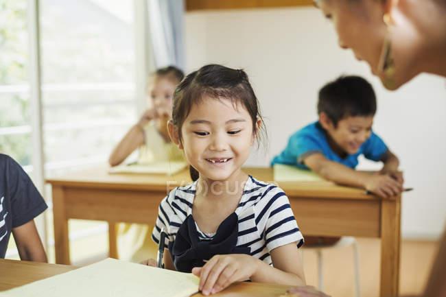 Kinder in einer Schulklasse mit Lehrer — Stockfoto