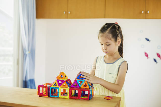 Girl building a structure with geometric shapes. — Stock Photo