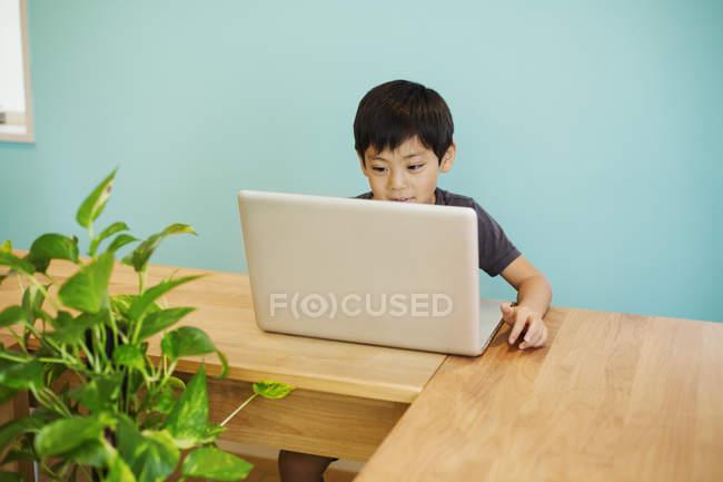 Ragazzo utilizzando un computer portatile in una classe . — Foto stock
