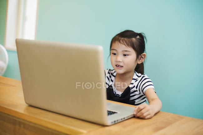 Fille assise à un ordinateur portable — Photo de stock