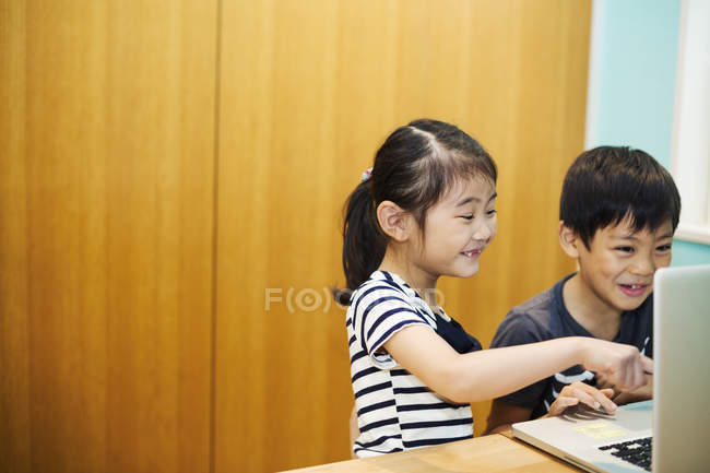 Children sharing a laptop computer. — Stock Photo