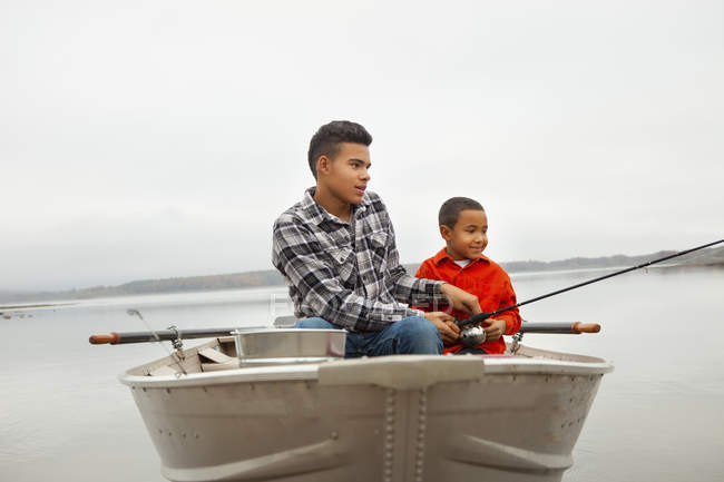 Two boys sitting fishing from a boat. — Stock Photo