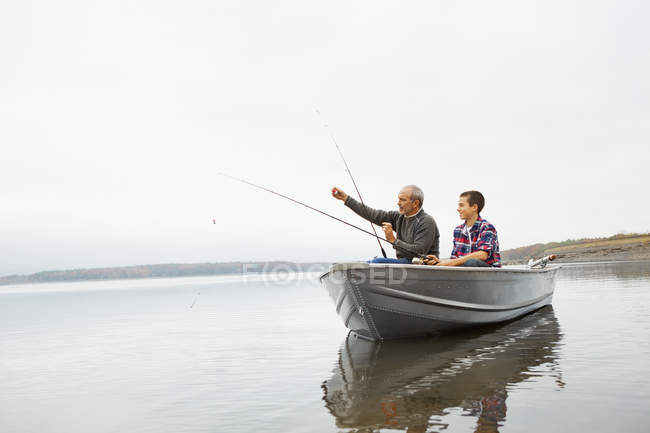Man and boy fishing from a boat. — Stock Photo