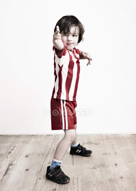 Garçon en chemise rayée et short de football — Photo de stock