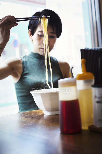 Woman eating ramen noodles — Stock Photo