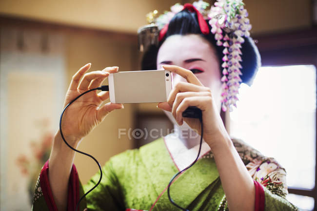 Traditional geisha taking a selfie. — Stock Photo