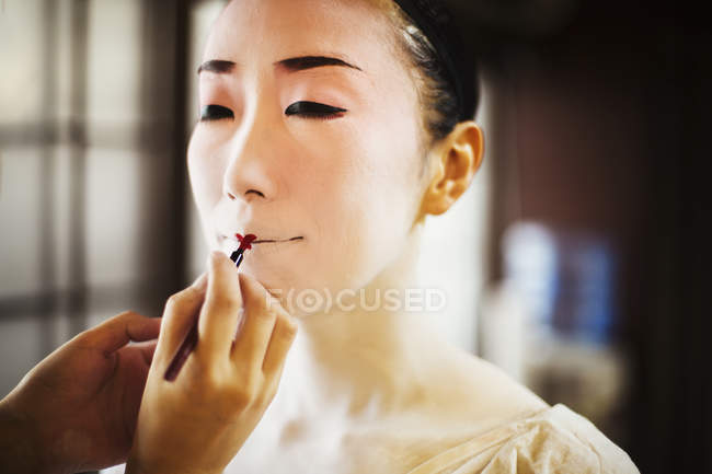 Geisha or maiko with a hair and make up artist — Stock Photo