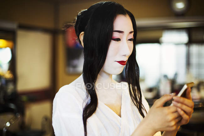 Geisha using a smart phone. — Stock Photo