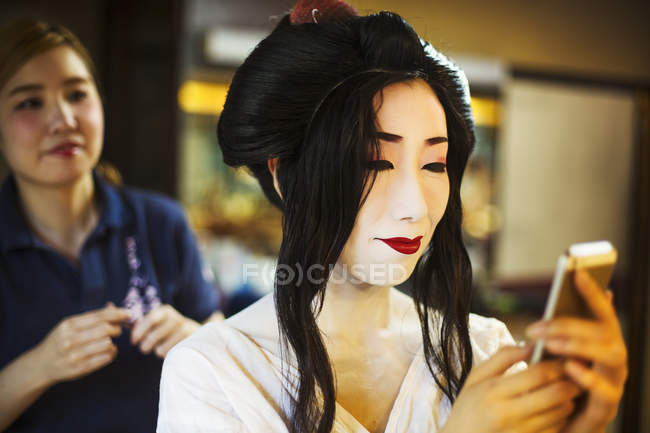 Geisha with a hair and make up artist — Stock Photo