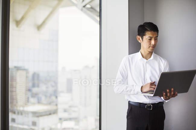 Бизнесмен с помощью ноутбука за окном — стоковое фото
