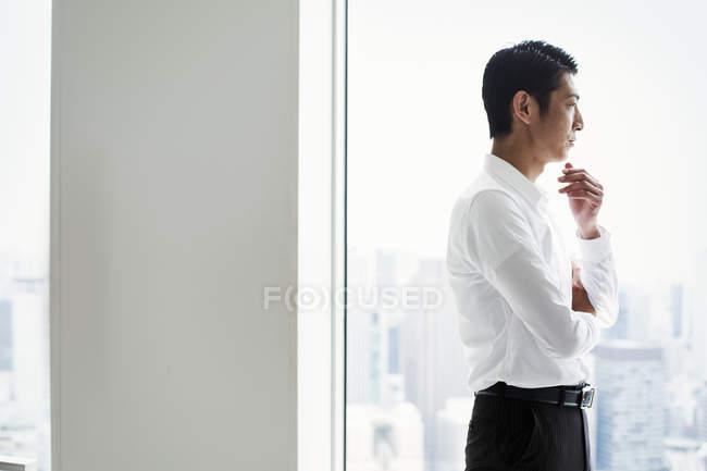 Бизнесмен в офисе, стоящий у окна — стоковое фото