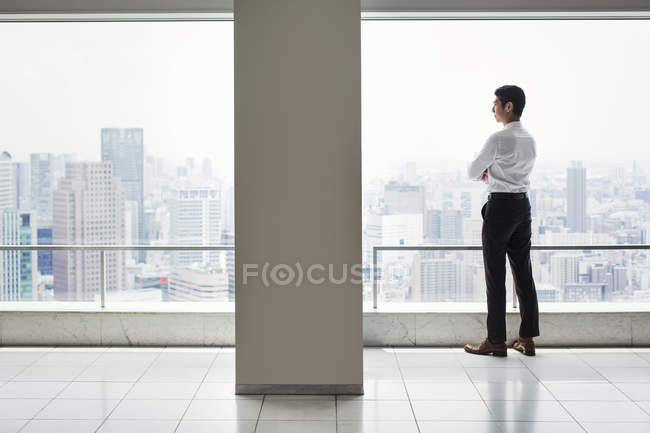 Hombre de negocios en la oficina de pie por la ventana - foto de stock