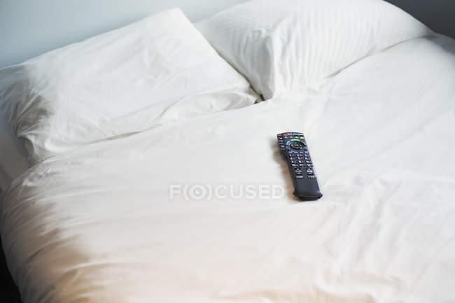 Telecomando sdraiato sul letto — Foto stock