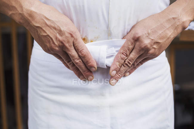 Master chef tying his apron. — Stock Photo