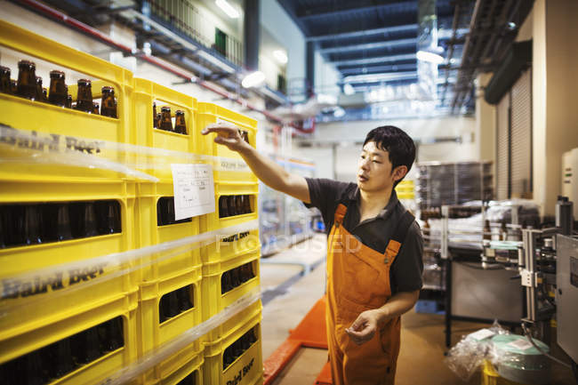 Worker labelling yellow plastic crates — Stock Photo