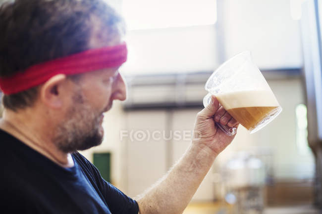 Brewer brewing beer and examining it. — Stock Photo