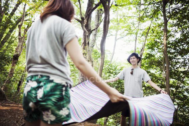 Жінка і чоловік тримає пікнік килимок — стокове фото