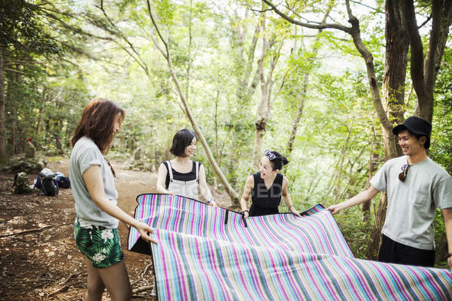 Women and man holding a picnic rug. — Stock Photo