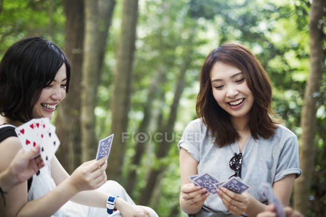 Women playing cards in a forest. — Stock Photo