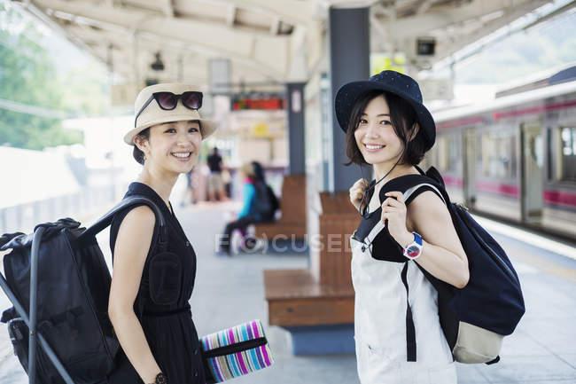 Mulheres de pé em uma plataforma em uma estação ferroviária . — Fotografia de Stock