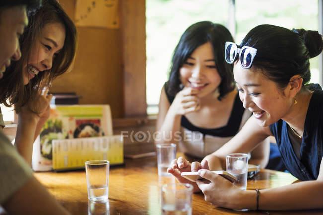 Mujeres y un hombre sentado en un café . - foto de stock