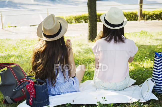 Women sitting on a lawn. — Stock Photo