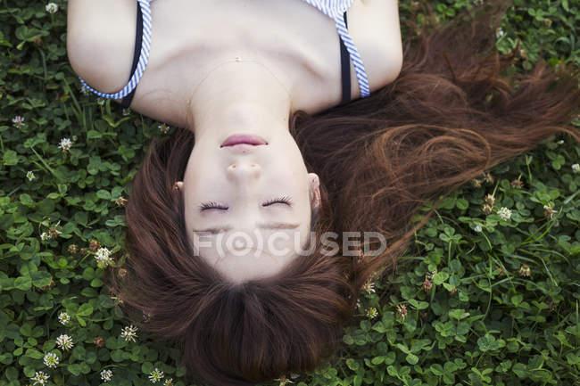 Женщина с длинными волосами лежит на газоне . — стоковое фото