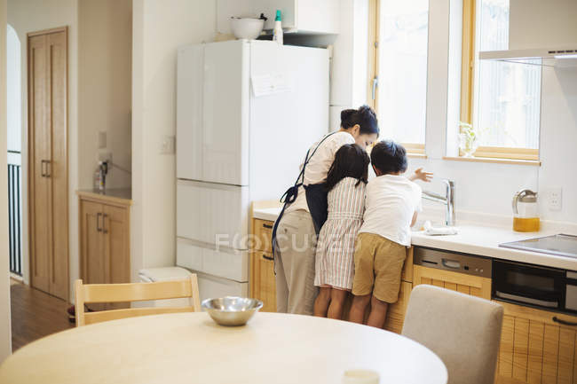 Mother and children at the sink in a kitchen. — Stock Photo