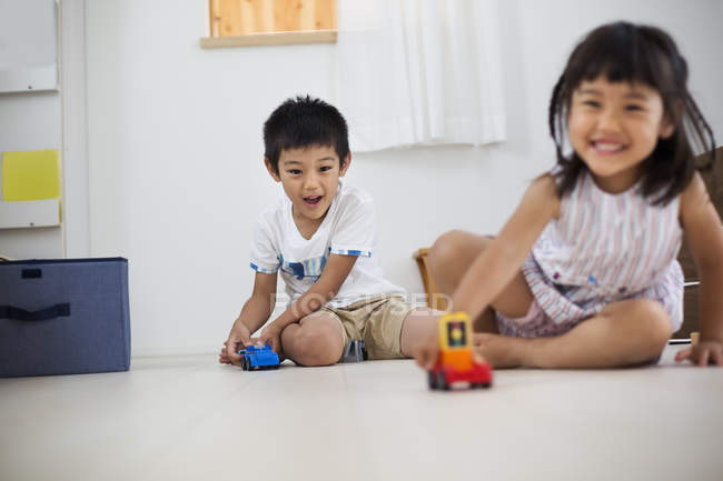 Children playing with toys on the floor. — Stock Photo