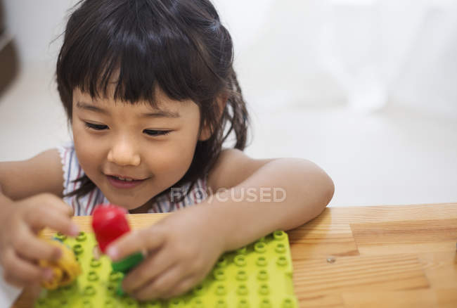 Girl playing with two dolls. — Stock Photo