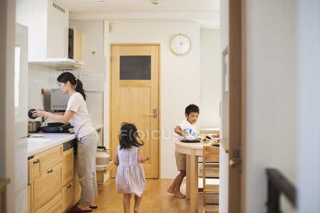 Woman and two children in kitchen — Stock Photo