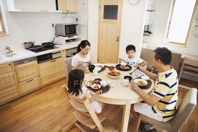 Family of two adults and two children eating — Stock Photo