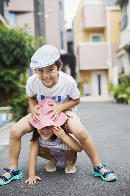 Boy and girl playing outdoors. — Stock Photo