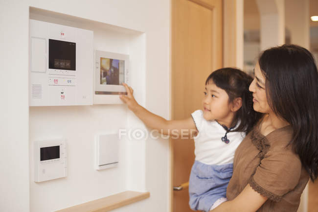 Woman and daughter looking at screen on the wall — Stock Photo