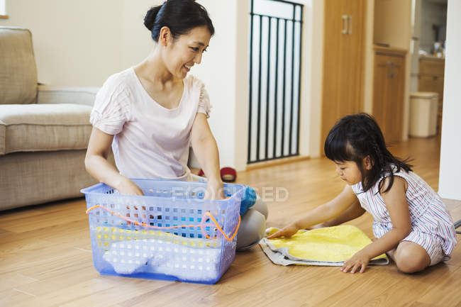 Woman and daughter folding clean laundry. — Stock Photo