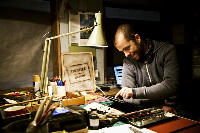 Man in his workshop using a digital tablet — Stock Photo