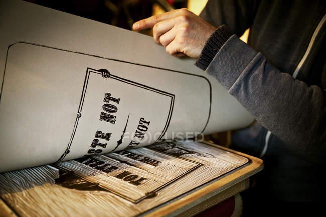 Signwriter lifting a sheet of imprinted card — Stock Photo