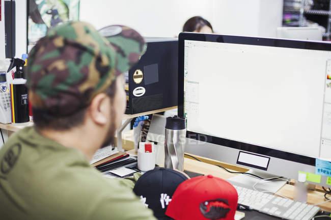 Hombre sentado en un escritorio usando una computadora - foto de stock