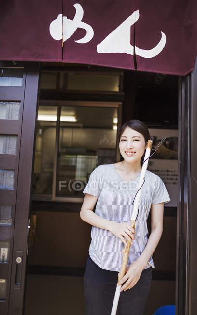 Frau steht vor der Tür eines Nudelladens — Stockfoto