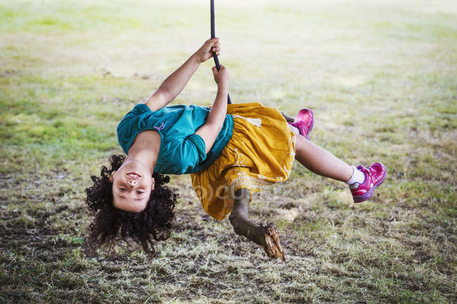Girl sitting on a tree swing. — Stock Photo