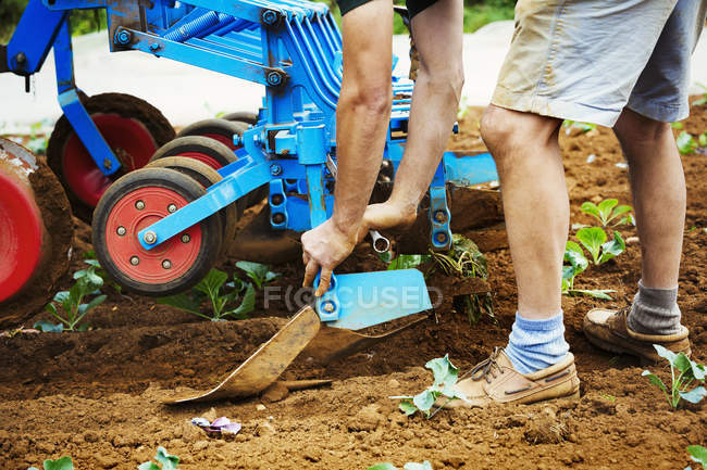 Man realigning a cultivator — Stock Photo