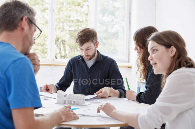 Men and two women seated at table — Stock Photo
