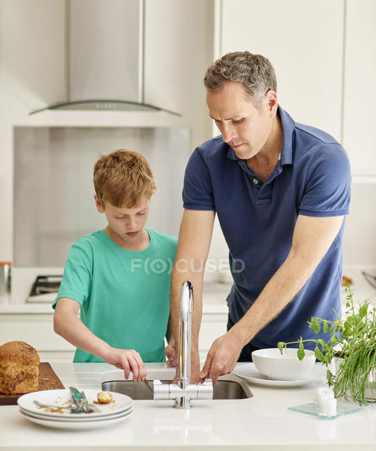 Man and young boy in kitchen — Stock Photo