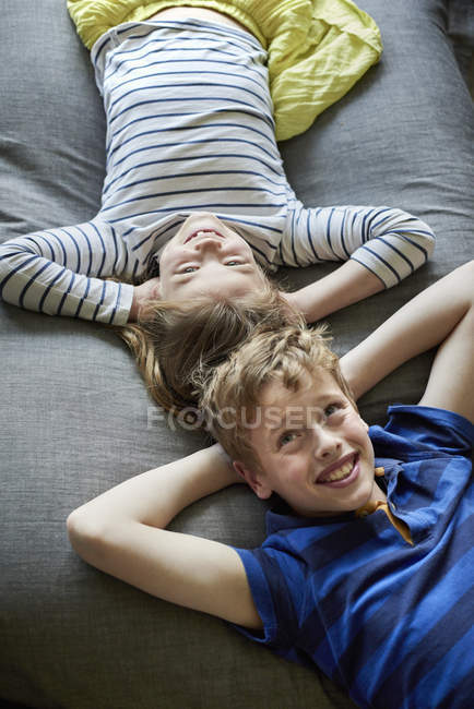 Boy and girl lying on sofa — Stock Photo