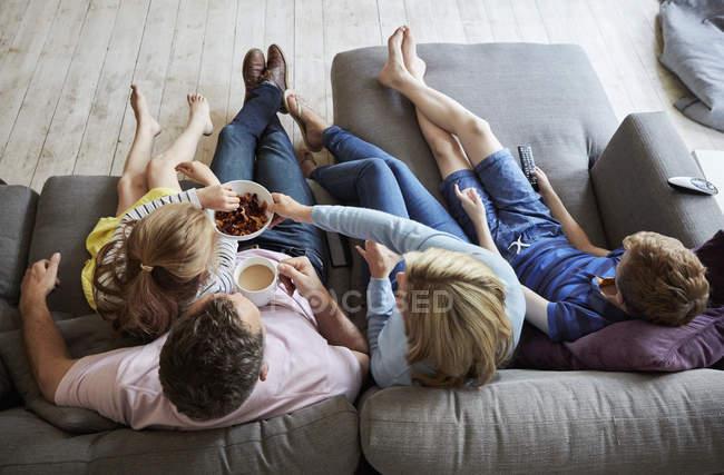 Семья дома, сидящая на диване вместе . — стоковое фото