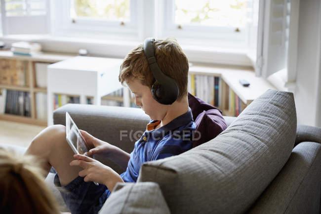 Хлопчик на дивані, використовуючи цифровий планшетний — Stock Photo