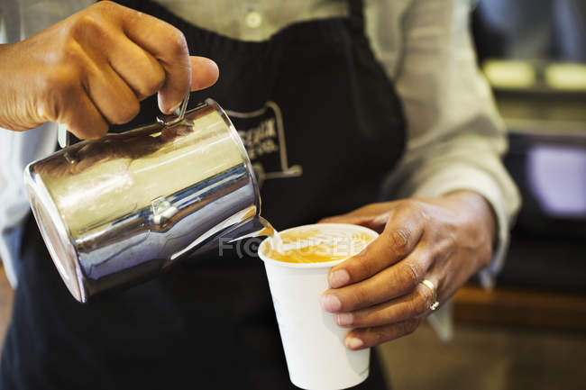 Hot milk being poured from a jug — Stock Photo